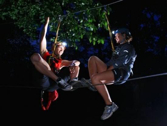 A couple go treetop trekking at night using headlights
