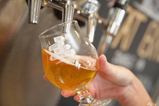 A glass of beer being poured from a beer tap