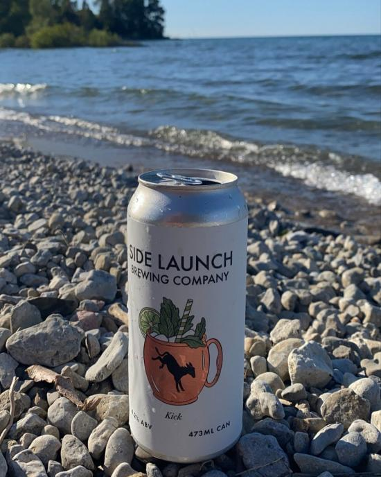 A can of beer resting on pebbles with a lake in the background