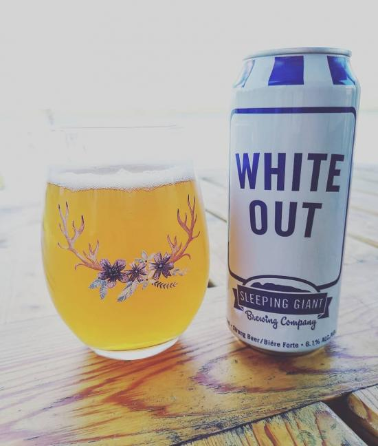 A beautifully adorned glass of beer beside a tall can of beer resting on a table