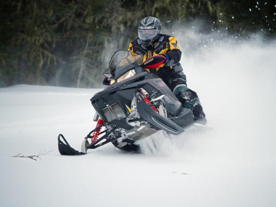 A lone snowmobiler rides swiftly as the snow flies behind