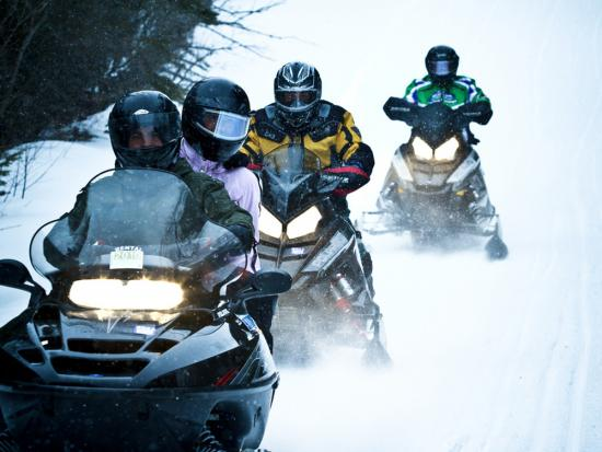 Four snowmobilers ride in a row