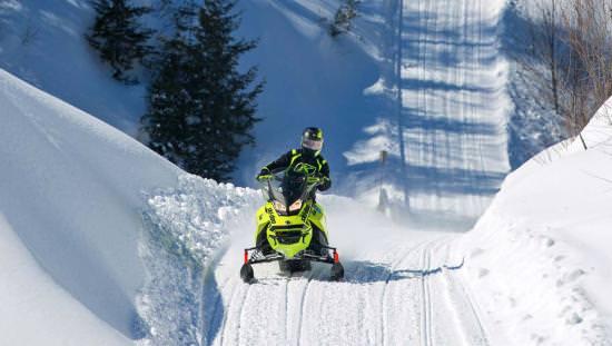 A snowmobiler rides over a snowy ridge along a snowmobile trail
