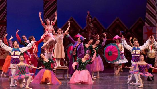 Un groupe de danseurs de ballet vêtus de costumes aux couleurs vives se produit sur scène