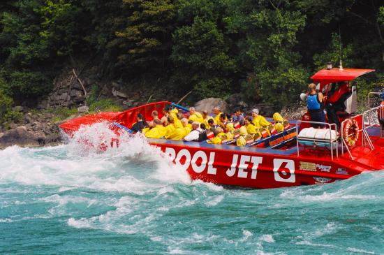 A jet boat in rough waters navigating through a gorge