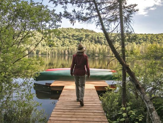 A woman walks onto a dock with canoes on it