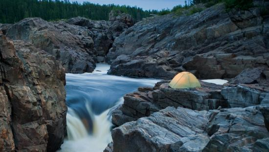 Backcountry campsite with a yellow tent beside rushing rapids
