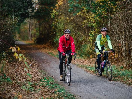 Two men smiling and cycling on a trail