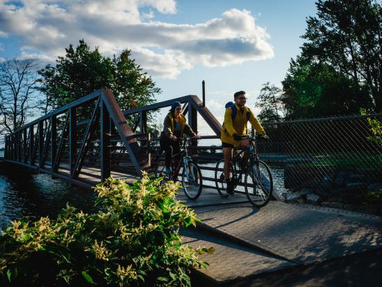 A man and a woman cycling over a small bridge
