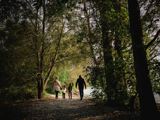 A family of four taking a stroll in a forest