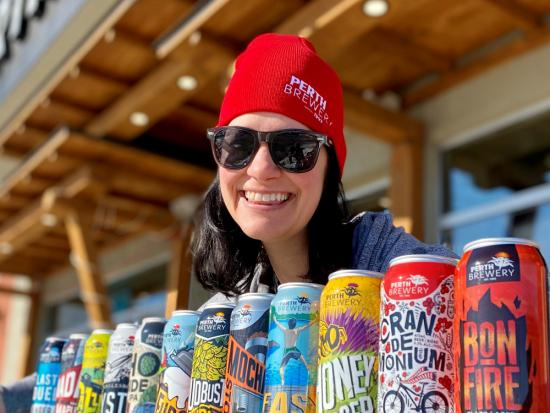 Une femme présente une rangée de canettes de bière artisanales uniques en petits lots