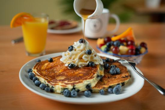 Maple syrup pouring over blueberry pancakes