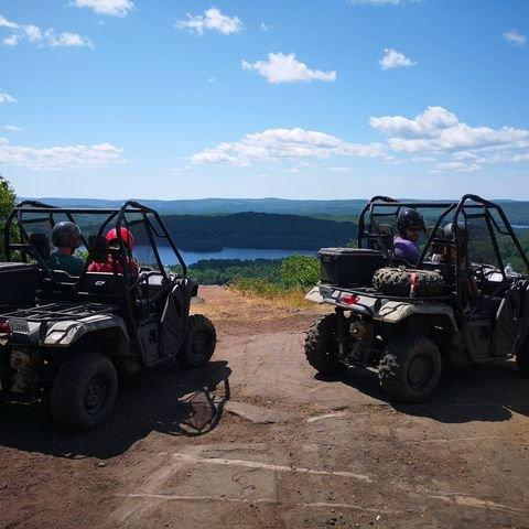 Two ATVs on a dirt trail overlooking a lake