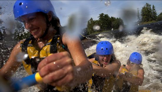 Close up of water splashing against paddlers on a whitewater raft