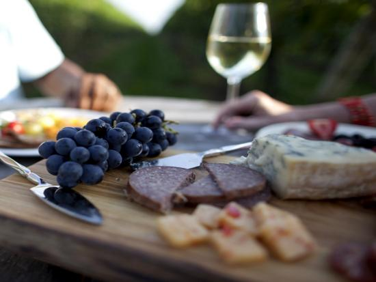 A couple enjoy an outdoor picnic of charcuterie, fruit and wine