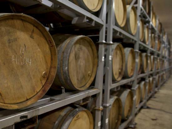 Une rangée de tonneaux de vin empilés dans une cave