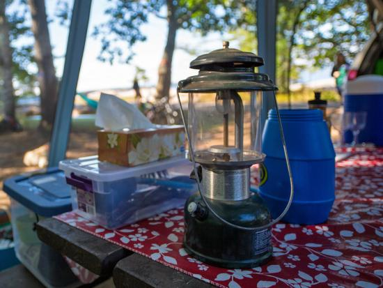 Dishes, a lantern and other camping supplies sit on a picnic table