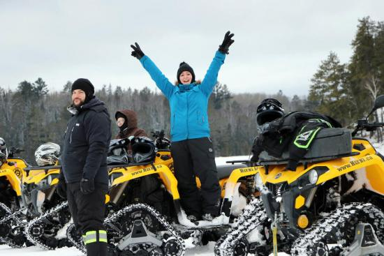 A woman standing, excitingly raises both hands in the middle of winter ATVs with 2 men off to her right side