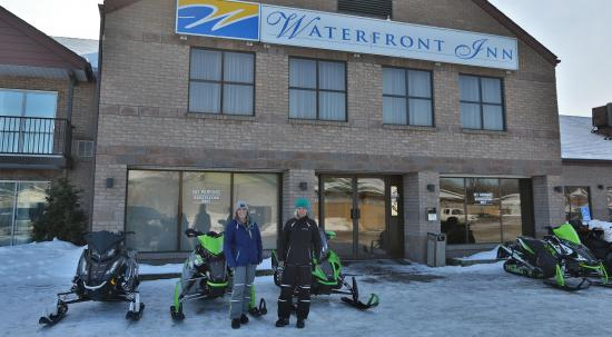 2 women standing in front of snowmobiles which are parked in front of the Waterfront Inn