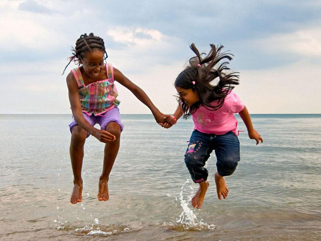 Two laughingchildren jump out of shallow water in front of a vastexpanse of water.
