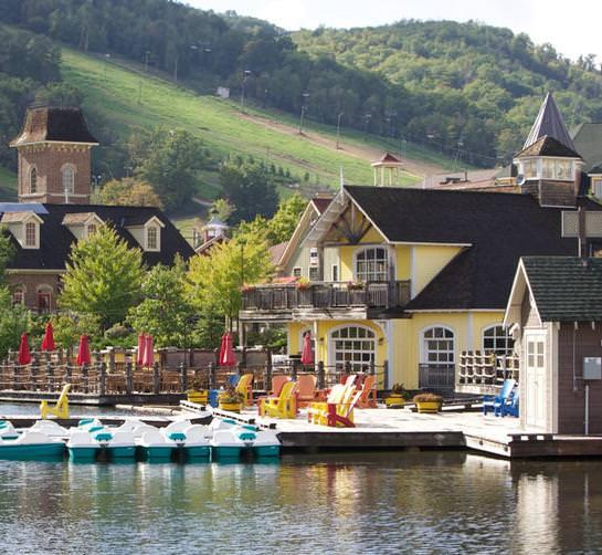 \Plusieurs restaurants et hébergements avec quais flottants entourant un plan d'eau avec pédalos amarrés.