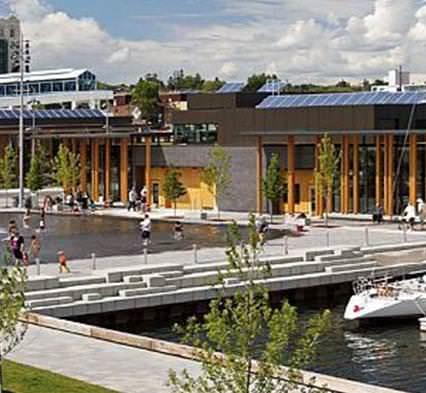 Un front de mer plein de gens se prélassant, marchant et pataugeant dans une piscine-fontaine, y compris une zone pour amarrer les bateaux, avec accès à un bâtiment communautaire