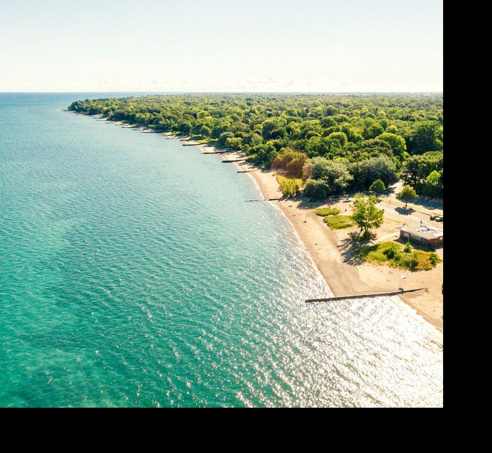 An aerial view of gorgeous blue green water and a long sandy beach