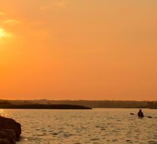 Une personne qui fait du kayak pendant un coucher de soleil.