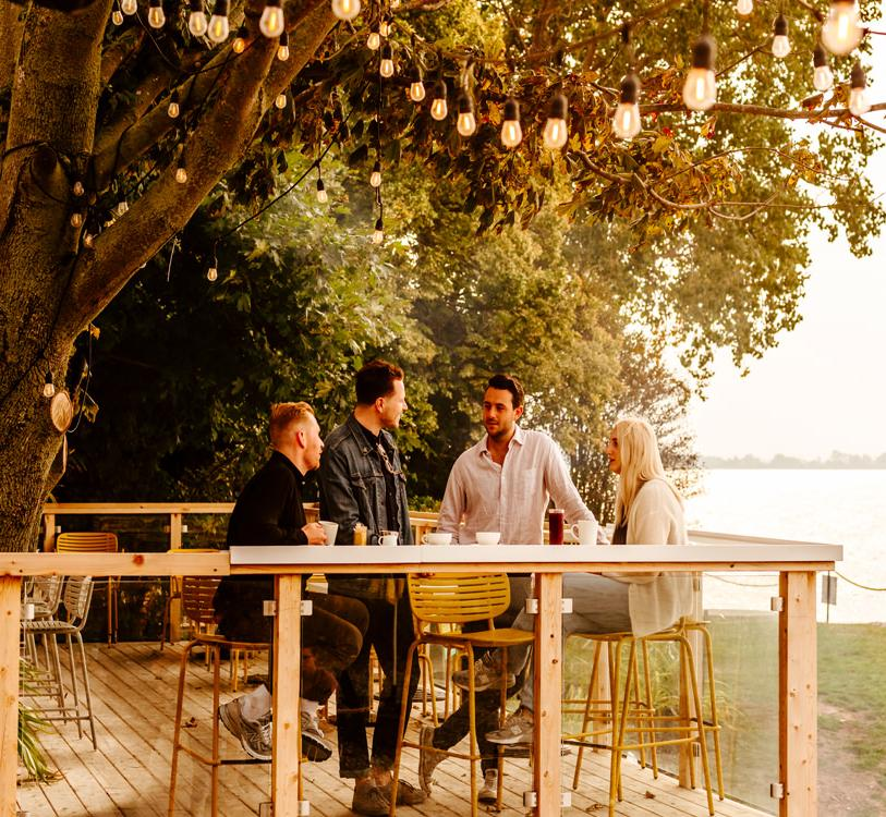 A group of four friends gather on an outdoor patio