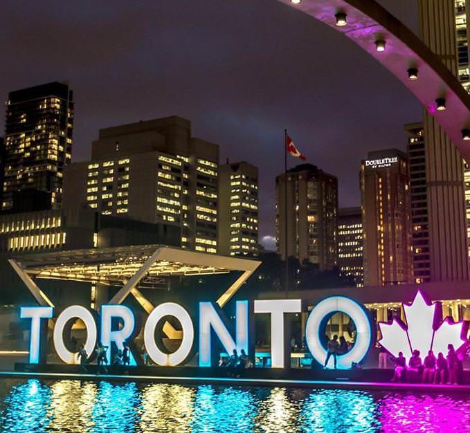 Groupe de personnes qui profitent de la soirée autour de la grande enseigne extérieure Toronto, qui est illuminée de multiples couleurs et constitue l'élément central de l'hôtel de ville, entourée de hauts édifices.