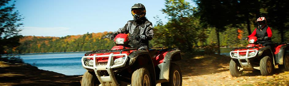 Two ATV riders on a lakeside trail