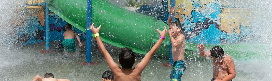A group of kids at a water park about to get splashed