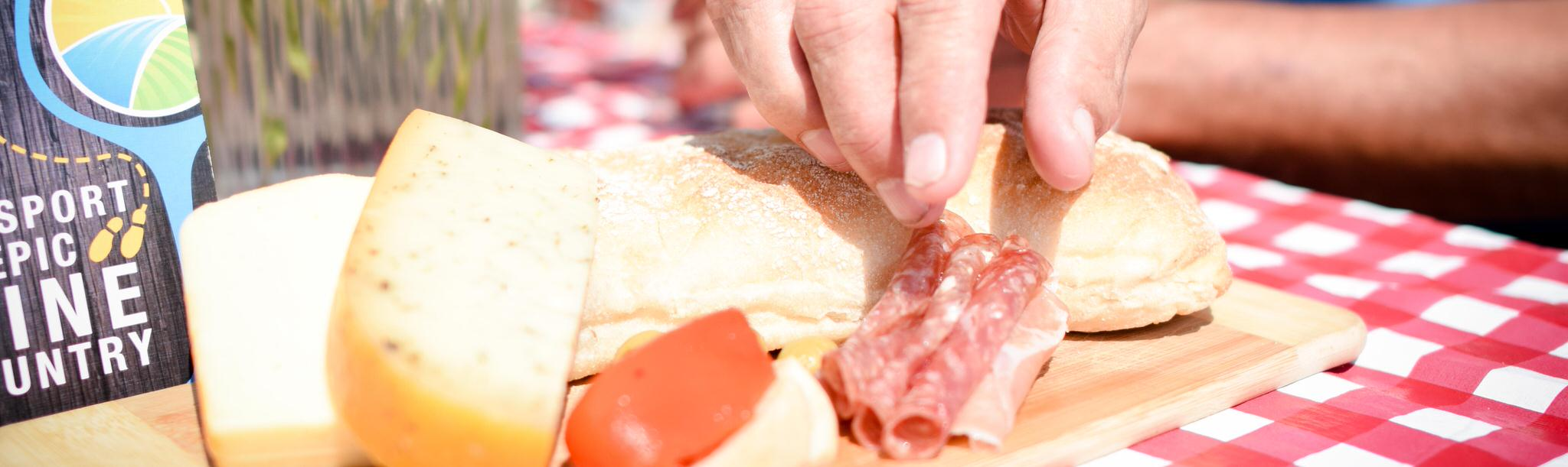 A person grabbing food from charcuterie plate