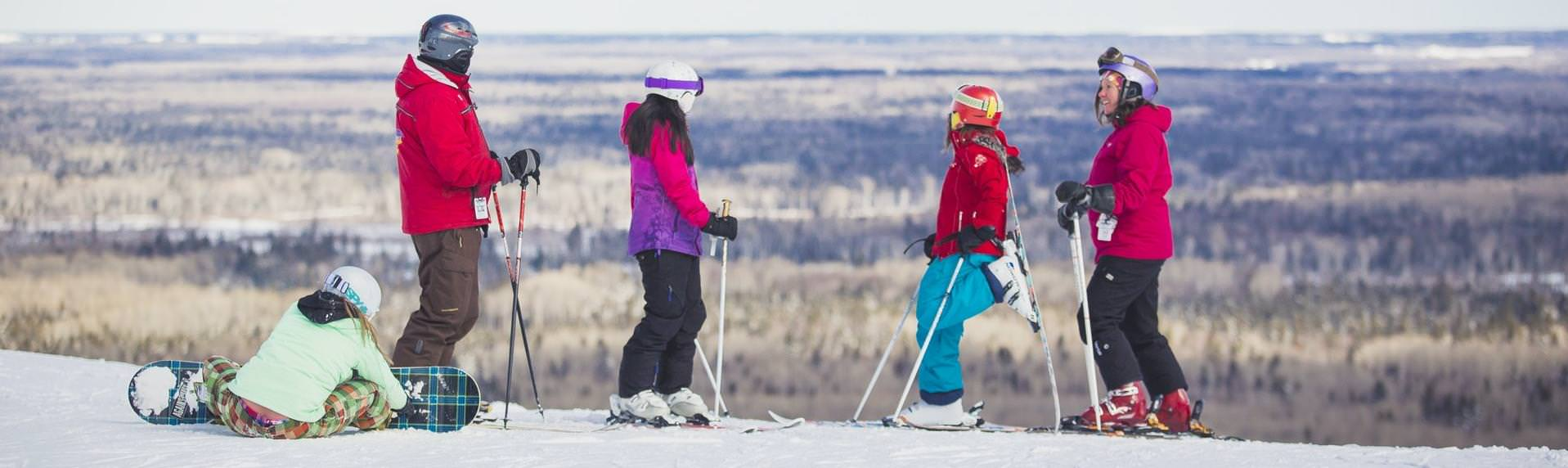 A family of four standing atop a ski hill