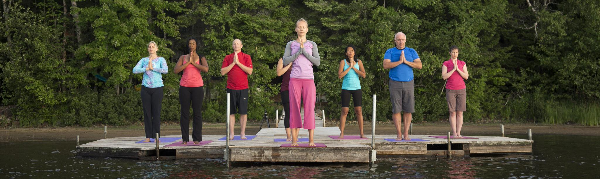 A group of people practicing yoga on a lakeside dock