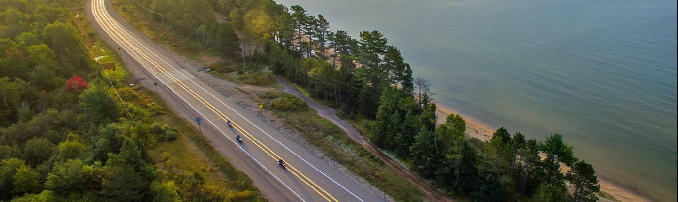 Three motorcyclists ride a highway alongside a massive lake