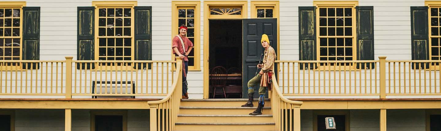 Two men in costume stand at the entrance of a heritage park