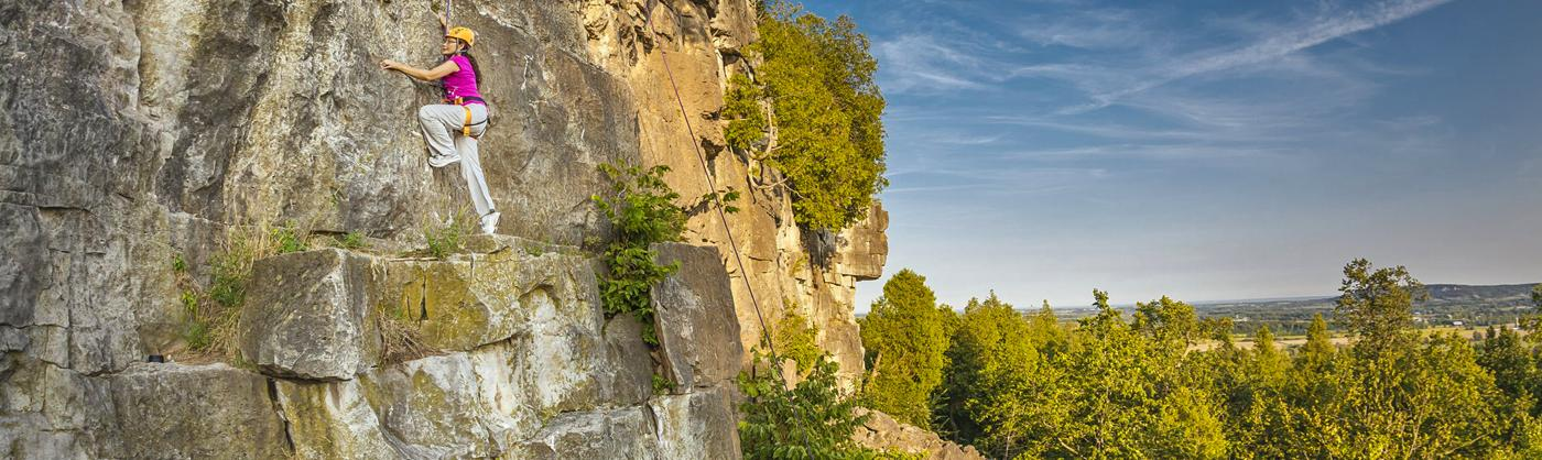 A woman climbs a rock wall