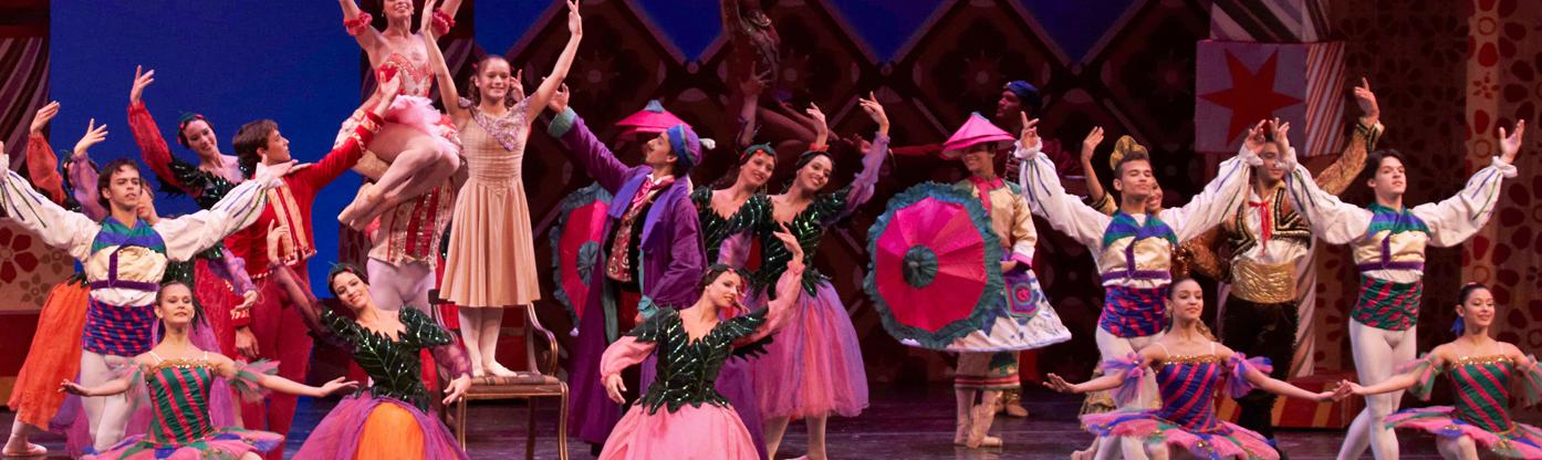 A group of ballet dancers in brightly coloured costumes perform on stage